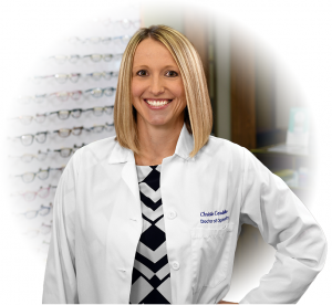 Portrait of Doctor Christie Cardellino standing in front of a rack of glasses